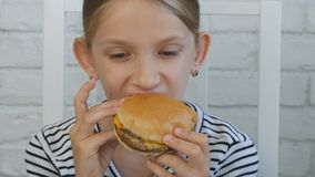 Child Eating Hamburger in Restaurant, Kid Eats Junk Fast Food Hungry Little Girl royalty free stock photography