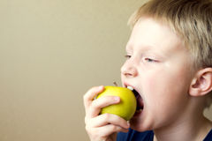 Child eating healthy food. Happy beautiful blond child (kid,boy,teen) eating healthy organic food - green apple stock photo