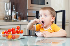 Child eating healthy food in kitchen Royalty Free Stock Photo