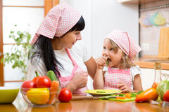 Child eating healthy food on kitchen. Child girl eating healthy food on kitchen royalty free stock images