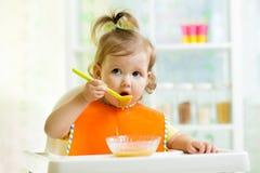 Child eating healthy food on kitchen. Kid eating healthy food on kitchen royalty free stock photo