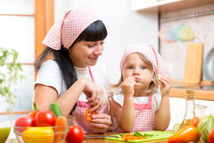 Child eating healthy food on kitchen. Child and mom eating healthy food on kitchen royalty free stock photography