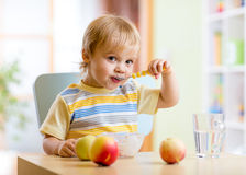 Child eating healthy food with with the left hand Stock Image