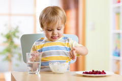 Child eating healthy food with a spoon Stock Photo