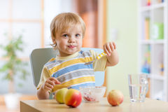 Child eating healthy food with a spoon at home Royalty Free Stock Image