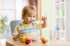 Child eating healthy food with a spoon at home Stock Photos