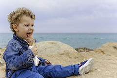 Child eating an ice cream on the beach Stock Photos