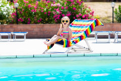Child eating ice cream at swimming pool. Little girl relaxing in colorful chair at outdoor pool of exotic tropical resort during family summer beach vacation Royalty Free Stock Photography