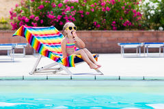 Child eating ice cream at swimming pool. Little girl relaxing in colorful chair at outdoor pool of exotic tropical resort during family summer beach vacation royalty free stock photos