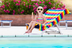 Child eating ice cream at swimming pool. Little girl relaxing in colorful chair at outdoor pool of exotic tropical resort during family summer beach vacation Stock Images
