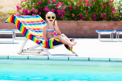Child eating ice cream at swimming pool. Little girl relaxing in colorful chair at outdoor pool of exotic tropical resort during family summer beach vacation Royalty Free Stock Images