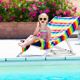 Child eating ice cream at swimming pool. Little girl relaxing in colorful chair at outdoor pool of exotic tropical resort during family summer beach vacation Royalty Free Stock Image