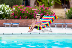 Child eating ice cream at swimming pool. Little girl relaxing in colorful chair at outdoor pool of exotic tropical resort during family summer beach vacation Stock Photos
