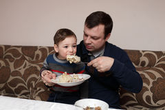 Child eating khinkali. Son eating khinkali from his father's hands Royalty Free Stock Photos