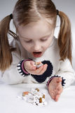 Child eating medication. Little girl eating medication by herself Stock Images
