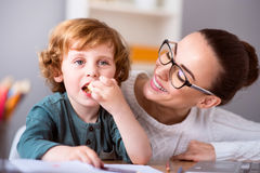 Child eating and mother looking at him Stock Image
