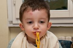 Child eating noodles Stock Image