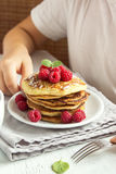 Child eating pancakes. Child eating healthy breakfast at home - pancakes with raspberries on plate with children hands Stock Photos