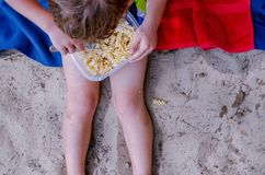 Child eating pasta on beach royalty free stock photo