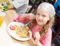 Child eating pasta at cafe at summer Stock Image