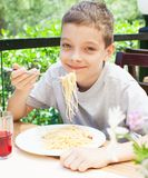 Child eating pasta at cafe at summer Stock Photography