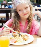 Child eating pasta at cafe at summer Stock Images