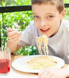Child eating pasta outdoors Stock Image