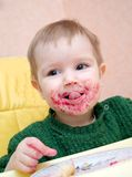 Child eating pie with currant. Royalty Free Stock Photo