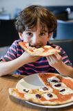 Child eating pizza royalty free stock images