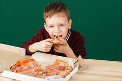 Child eating pizza slice from the box close up photo. Children eat Italian pizza in the cafe. School boy is eating pizza for lunch. Child unhealthy meal concept royalty free stock photo
