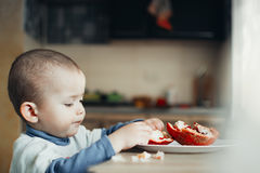 A child eating a pomegranate Stock Photo