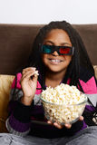 Child eating popcorn watching 3d movie Royalty Free Stock Images