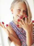 Child eating raspberries Stock Photos