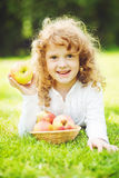 Child is eating red apple in summer park. Royalty Free Stock Images
