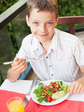 Child eating salad at a cafe Royalty Free Stock Photos