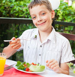 Child eating salad at a cafe Royalty Free Stock Photo