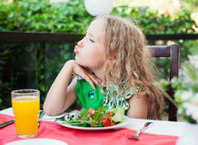Child eating salad at a cafe Royalty Free Stock Images