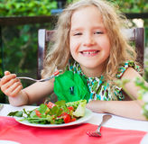 Child eating salad at a cafe Royalty Free Stock Photography