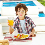 Child eating salad and drinking juice Royalty Free Stock Photography