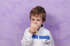 Child eating sandwich. Children dressed in white on a purple background eats a sandwich stock photography