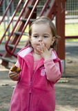 Child eating snack. Portrait of a little girl in a pink vest enjoying a sweet snack in the outdoor playground Royalty Free Stock Photography
