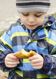Child eating snack on street Stock Images