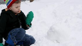Child Eating Snow and Making a Snow Ball stock video footage