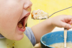 Child eating soup Stock Images