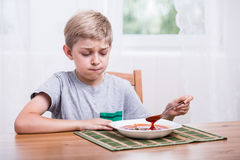 Child eating soup with disgust. Picky eater child eating soup with disgust Royalty Free Stock Image