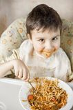 Child eating spaghetti with vegetables. Kid having fun eating. Brown haired boy with face covered in sauce. Weekend, warm and cozy royalty free stock image