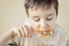 Child eating spaghetti with vegetables. Kid having fun eating. Brown haired boy with face covered in sauce. Weekend, warm and cozy. Scene in the kitchen stock photography
