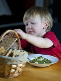 Child eating spinach soup and crispbread. Young caucasian boy eating spinach soup and crispbread Stock Photos