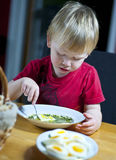 Child eating spinach soup and crispbread. Young caucasian boy eating spinach soup and crispbread Royalty Free Stock Images