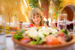 Child eating in summer cafe Stock Photos